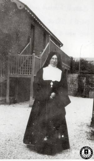 Sister-M-Edward-in-front-of-Priest\'s-cottage 1930