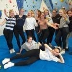 Year 10 Geography Group at Calshot Activities Centre in front of a climbing wall.